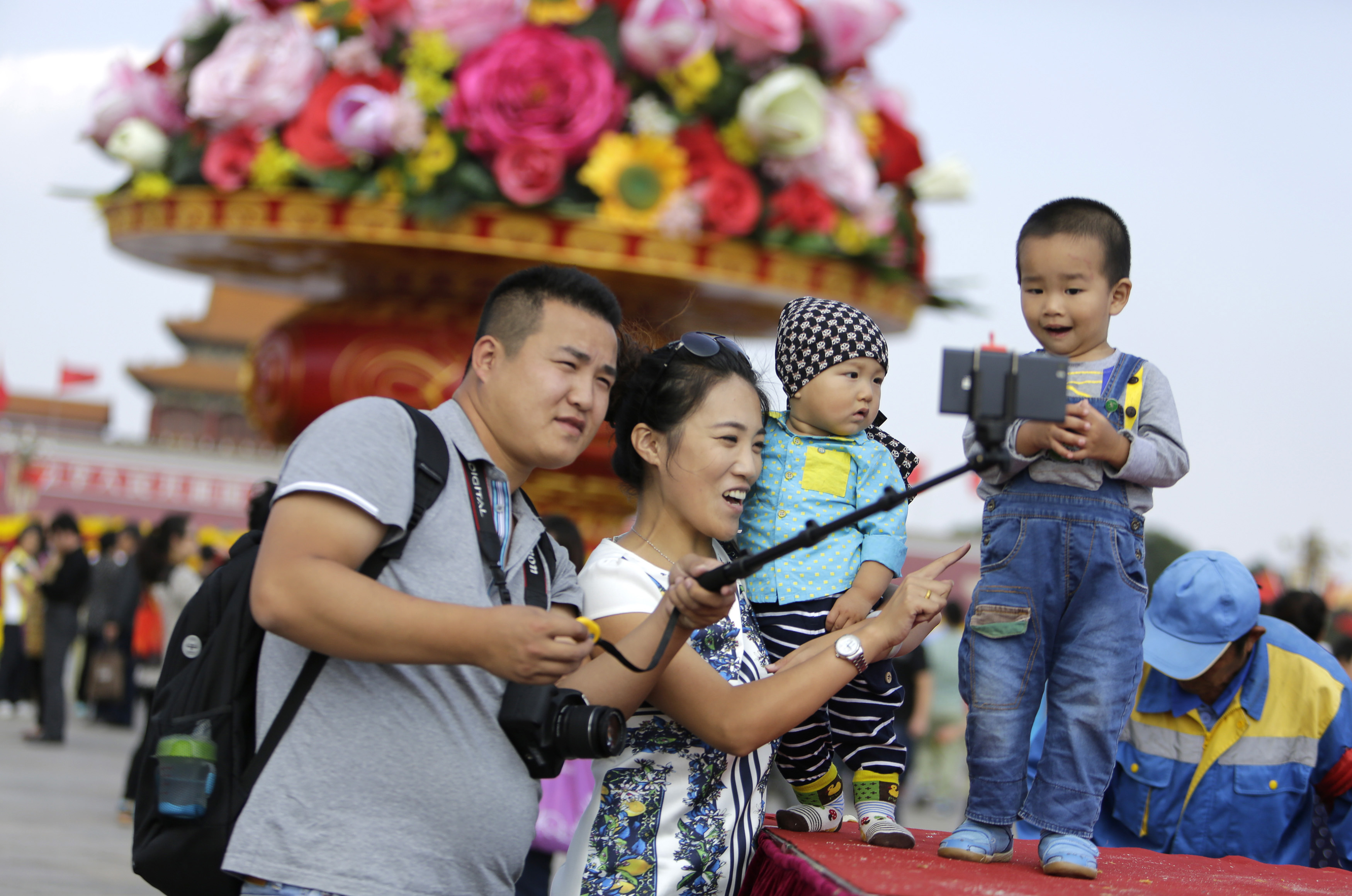 "A family takes a ""selfie"" next to a boy in front of a giant basket of flowers on display at Tiananmen Square for the upcoming 65th National Day celebrations on Wednesday, in Beijing"
