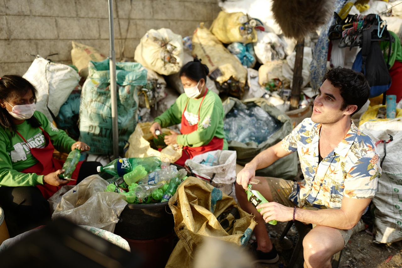 Daren Criss (right) helps sort plastic bottles to be recycled. (Global Citizen/Ryan Gall)