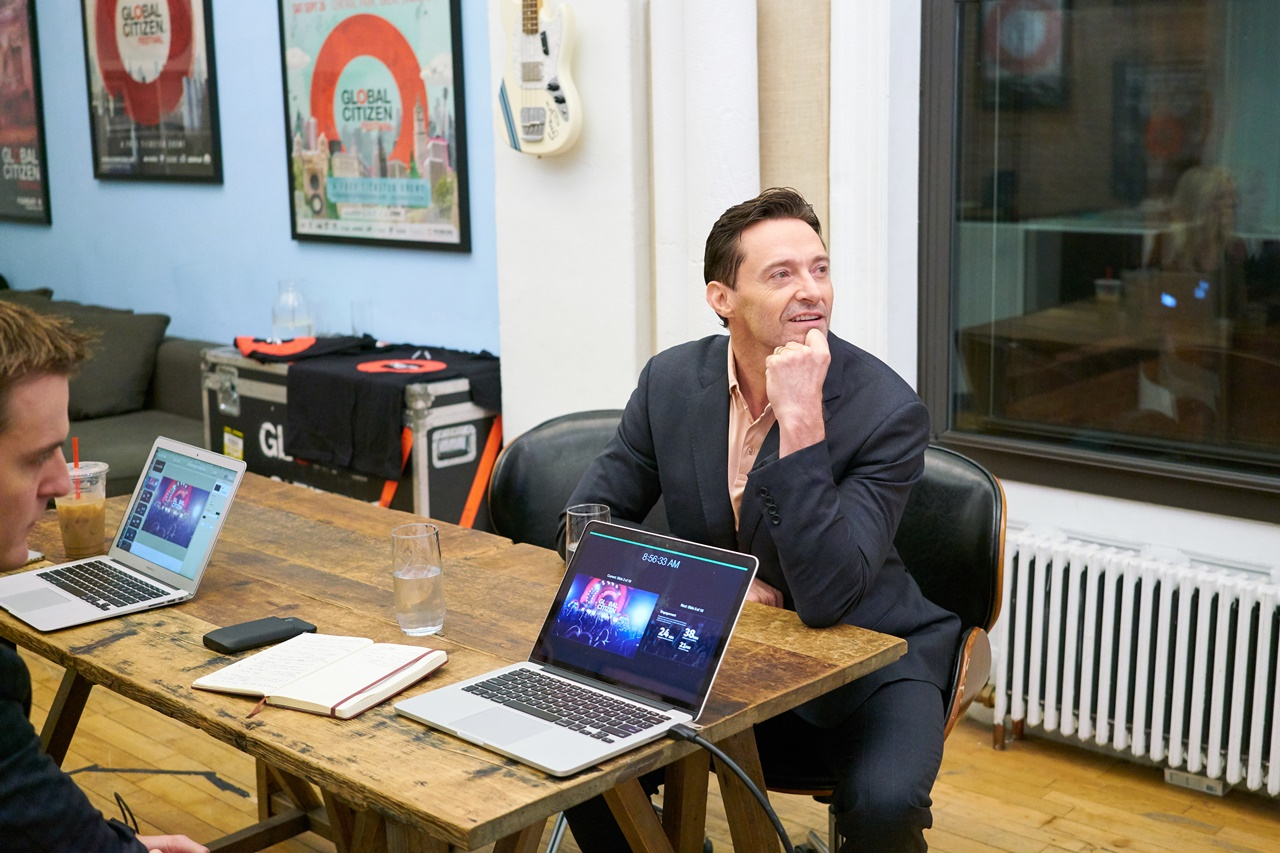 Hugh Jackman listens as the Global Citizen team brief him on responsible sourcing. (Global Citizen/Pip Cowley)