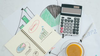 Closed up and soft focus on pen laying on paperwork with calculator for summary income or profit at office desk.