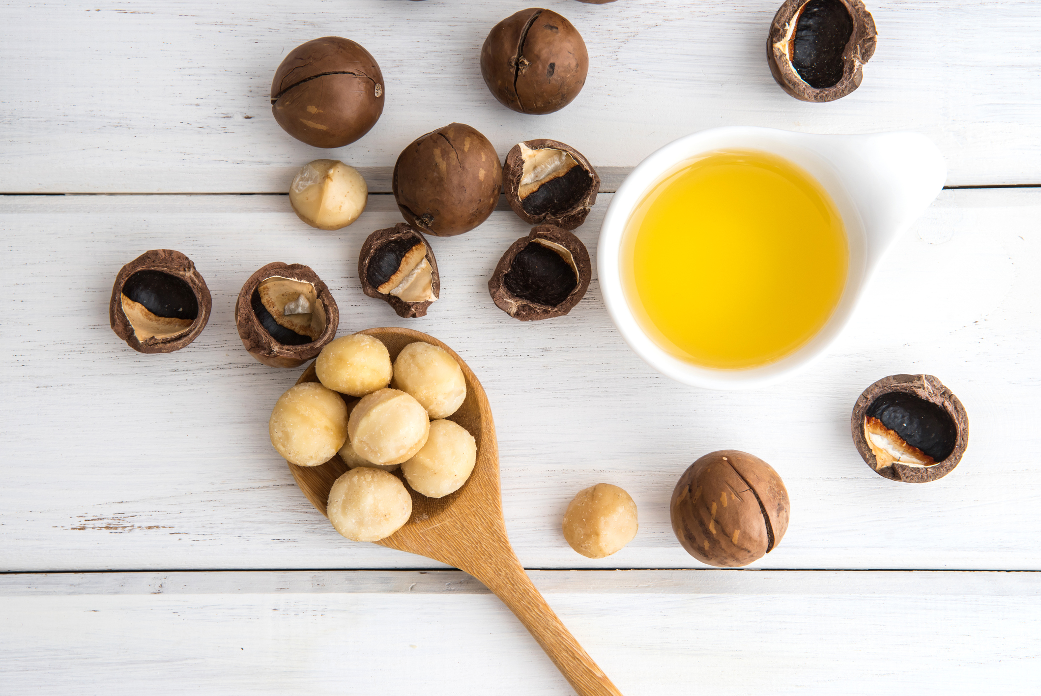 Macadamia Nut Oil and peeled macadamia nut on white table ,use for Healthy Skin and Hair and Natural Healing Oil Treatment , overhead and top view