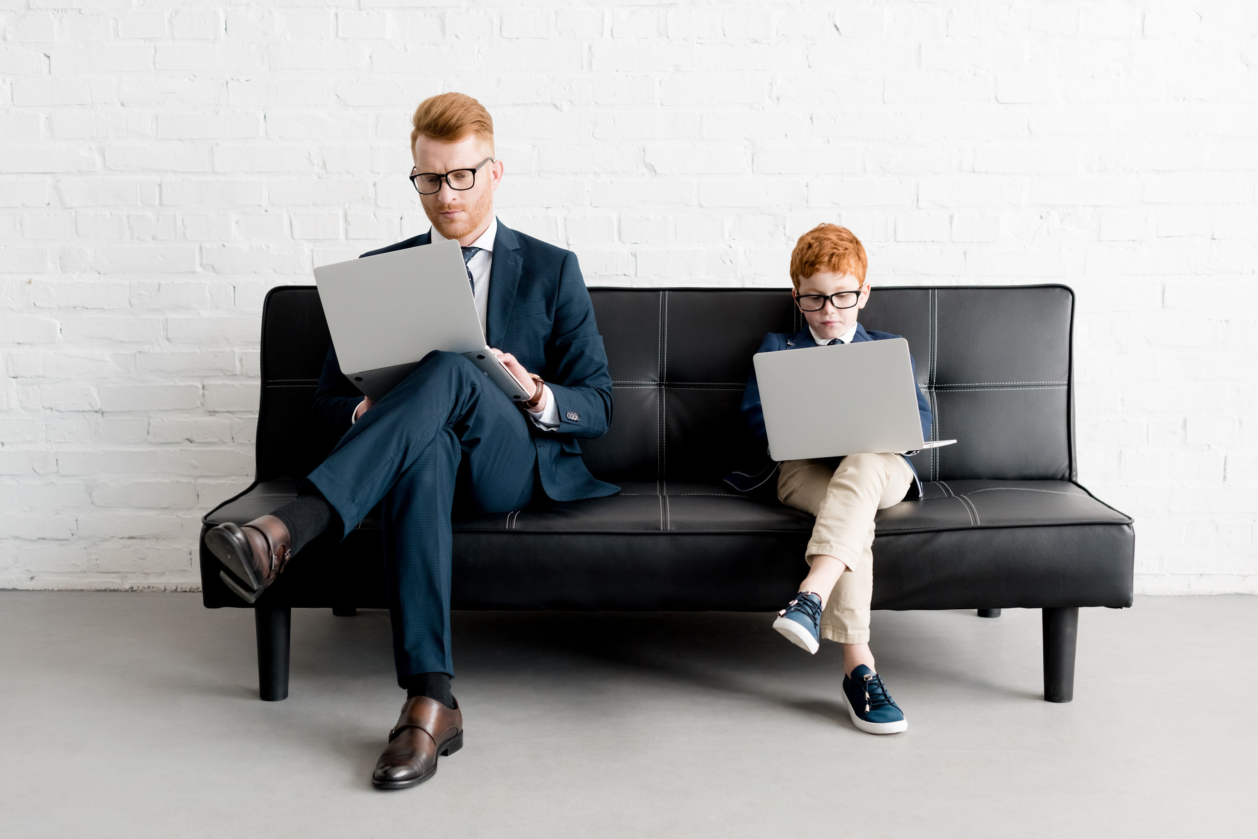 serious father and little son businessmen wearing eyeglasses and using laptops