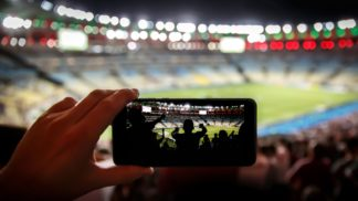 Using,A,Smartphone,At,A,Soccer,Stadium.,Silhouette,Of,Football